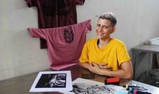 Estudante posa com algumas gravuras produzidas por ela.